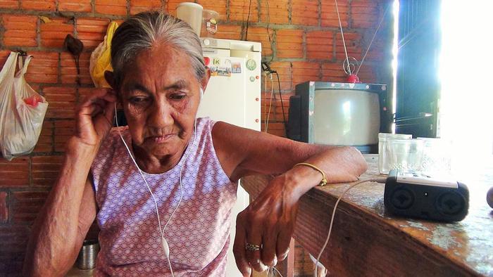 Eufrásia Ferreira, indígena Guató, na cozinha de sua casa, escuta registro da língua de seu povo, município de Corumbá, Mato Grosso do Sul. Foto: Gustavo Godoy, 2016.