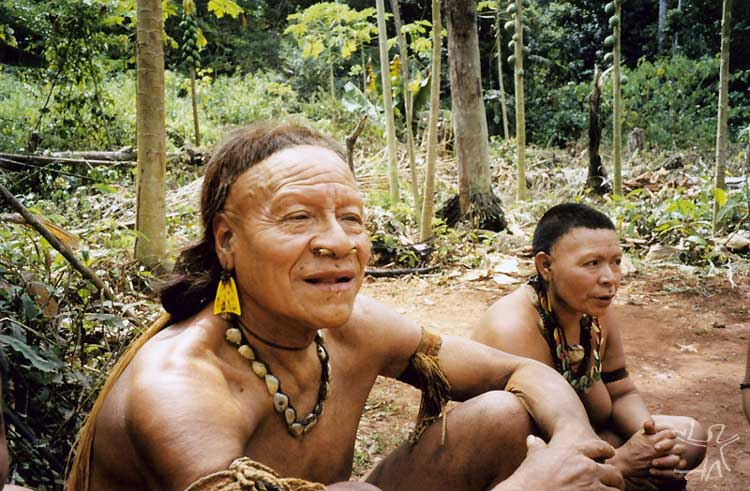 Kunibu [foreground] in front of the maloca. Photo: Adelino de Lucena Mendes, 2002.[b]