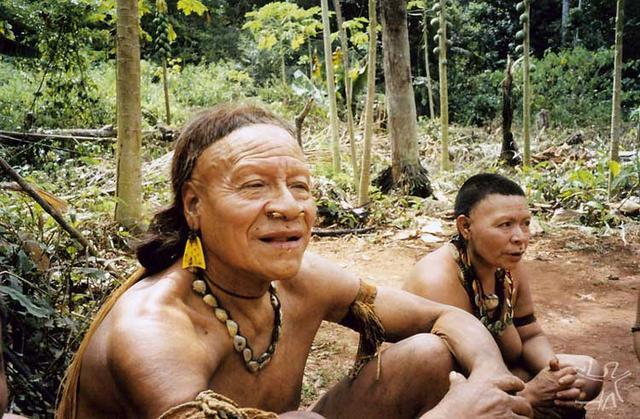 Kunibu em primeiro plano, sentado em frente à maloca. Foto: Adelino de Lucena Mendes, 2002.