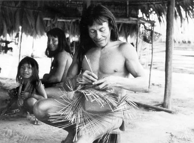O aparai Mikita fazendo uma cesta em aldeia no Rio Paru de Leste; ao fundo, sua esposa wayana. Foto: Daniel Schoepf, 1976.