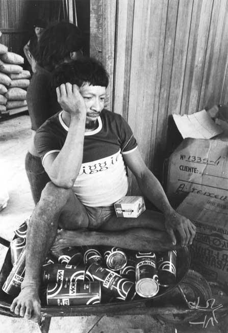 Kãyipayerä sentado em cima de latas de óleo na casa do chefe do Posto Indígena Ipixuna. Foto: Eduardo Viveiros de Castro, 1982.