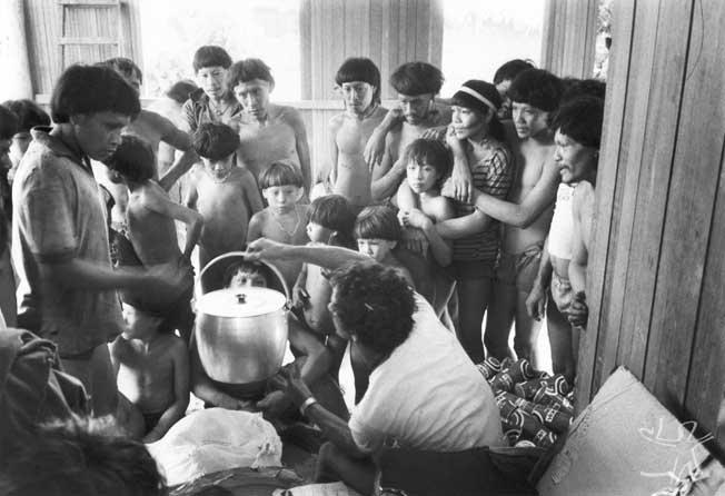Chefe do Posto Indígena Ipixuna (Eliezer G. da Silva) distribuindo bens encomendados pelos índios, comprados em Altamira com o dinheiro resultante da venda à FUNAI de seu artesanato. Foto: Eduardo Viveiros de Castro, 1982.