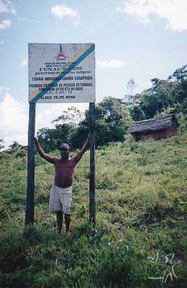 Capitão Felipe Bone com placa da aldeia com seu nome (TI Lagoa Comprida). Foto: Peter Schröder, 2000