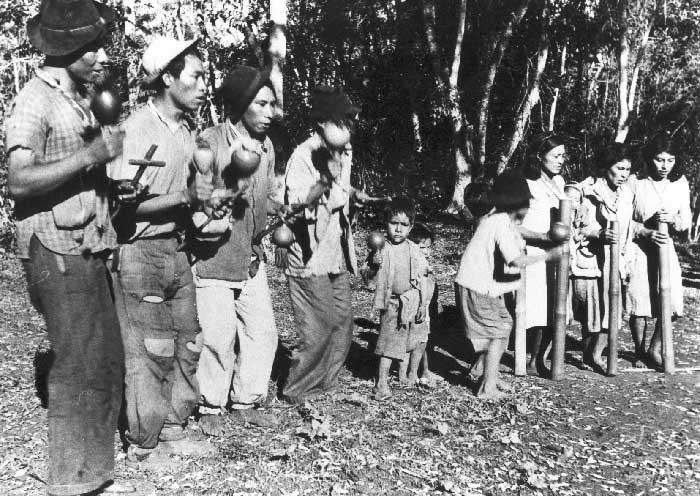 Kaiowa entre instrumentos tradicionais guarani e uma cruz do cristianismo. Foto: Egon Shaden, 1949.