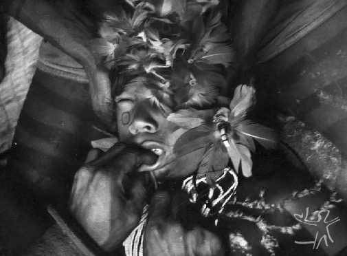 A primeira iniciação dos meninos Karajá se dá por volta dos 5 anos de idade. Consiste na perfuração do lábio inferior, que irá receber um adorno. A perfuração é feita com a clavícula de um macaco, e se dá na presença dos pais. Fotos: Claudia Andujar/s.d.