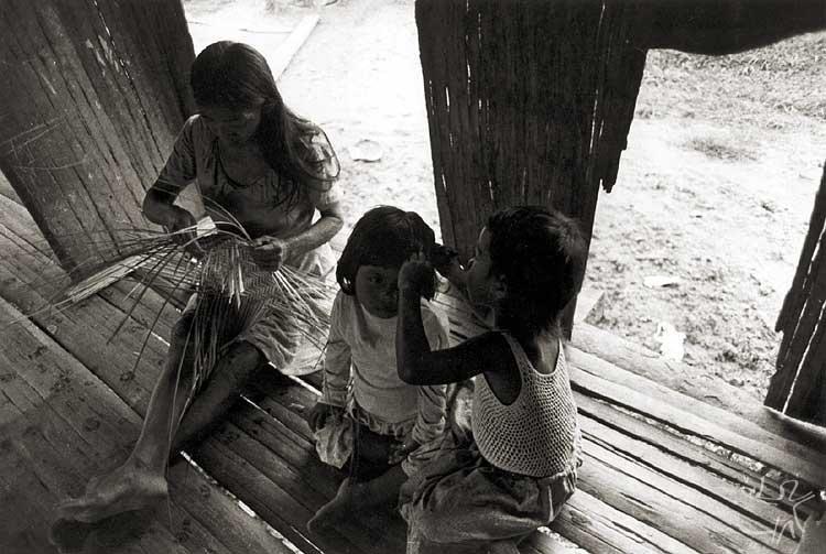Mulher confecciona um cesto enquanto crianças catam piolho. Foto: Nietta Linderberg Monte, 1984.