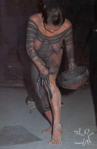 Mulher se pinta de preto com extrato de genipapo, pois seu filho completou um ano de idade e ela vai novamente participar das atividades cotidianas da aldeia. Foto: Gustaaf Verswijver, 1991.