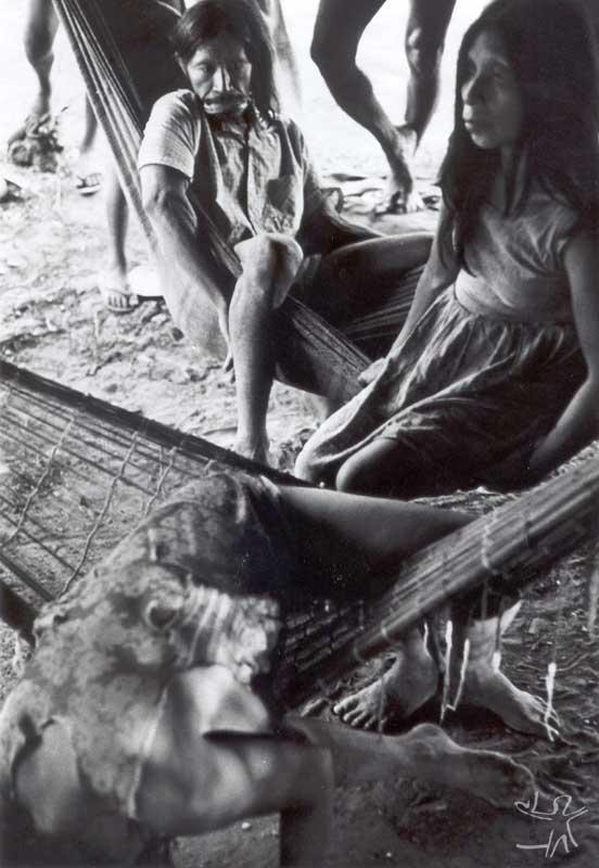Tapayuna na aldeia suyá (mulher inclinada na rede sofre um ataque atribuído ao trauma de ter disputado sua mãe morta, na qual tentava mamar quando pequena, com um urubu). Foto: Eduardo Biral, 1985.