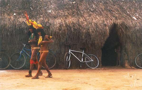 Mulheres kuikuru na aldeia Matipu por ocasião da festa Itão Kuegu (Yamurikumã), tendo ao fundo uma casa comunal. Foto: Camila Gauditano, 2001.