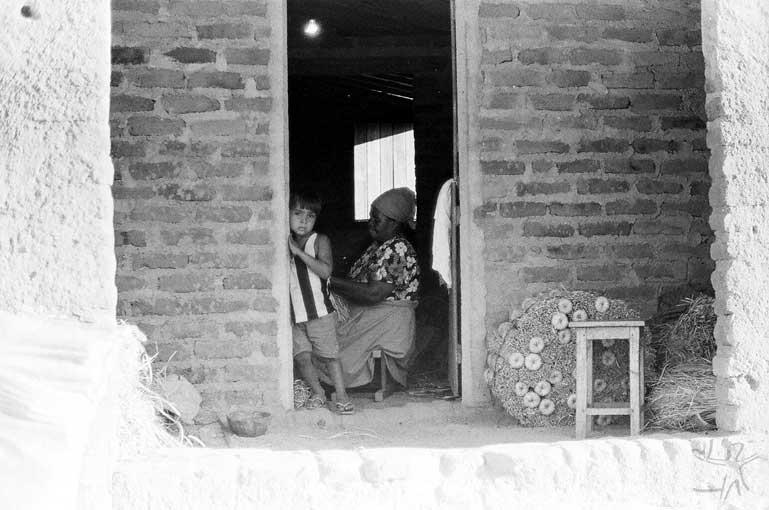 Avó e neta na sala de casa durante a produção de vassouras de palha de buriti. Foto: José Maurício Arruti, 1994.
