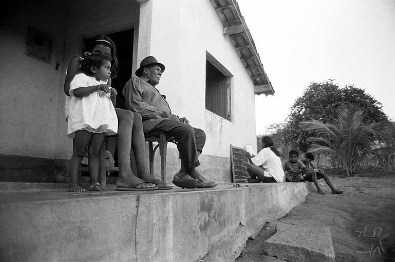 Aspecto de grupo residencial (constituído pela casa de patriarca, cercada pelas casas de filhos casados), com avô e netos na calçada. Foto: José Maurício Arrutti, 1994.