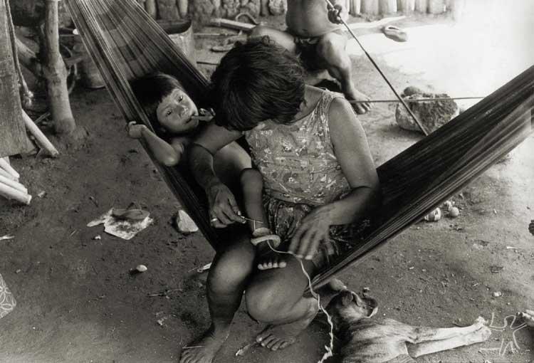 Mulher tecendo tornozeleira em seu filho. Foto: Antônio Carlos Moura, s/d.