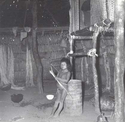 Criança Canela Ramkokamekrá no interior de uma habitação na aldeia do Escalvado. A cama elevada é de uma moça recém-casada sem filhos, para que apenas seu marido possa vê-la. Foto: Willian Crocker, 1969.