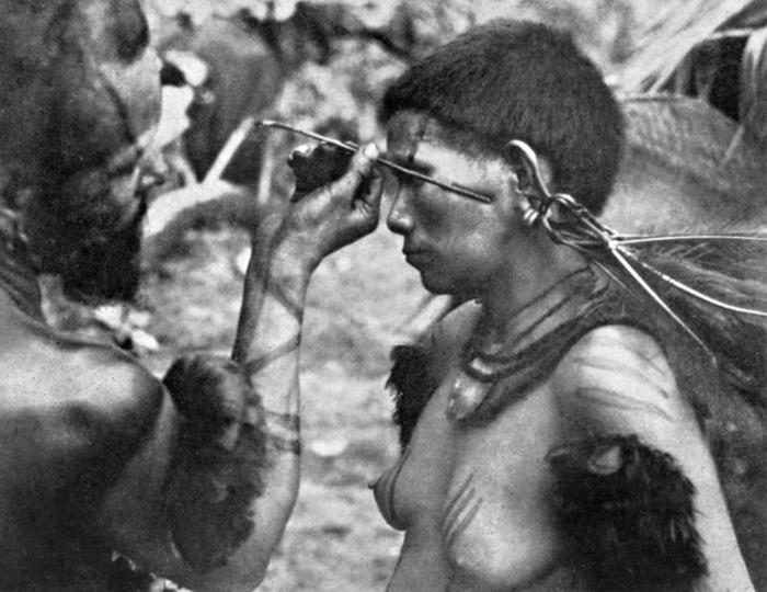 Mitoponepá adornando o rosto de sua esposa Huarepatá com sumo de jenipapo, incolor, que depois de seco se torna preto-azulado. Com um pauzinho envolvido em algodão faz desenhos delicados de formas geométricas; a pintura própria para homens é larga, cobrin