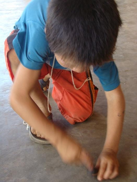Kadu roda seu peão feito com semente de tucum. Aldeia Tuba Tuba. Foto: Paula Mendonça/ISA, 2009.