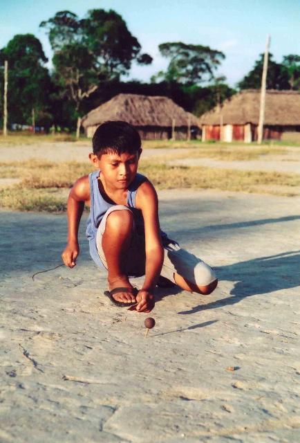 Menino wapishana brinca com pião feito de tucumã. Foto: Renata Meirelles.