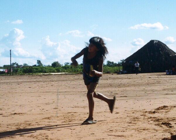 Menino xavante joga peteca no patio da aldeia. Foto: Renata Meirelles.