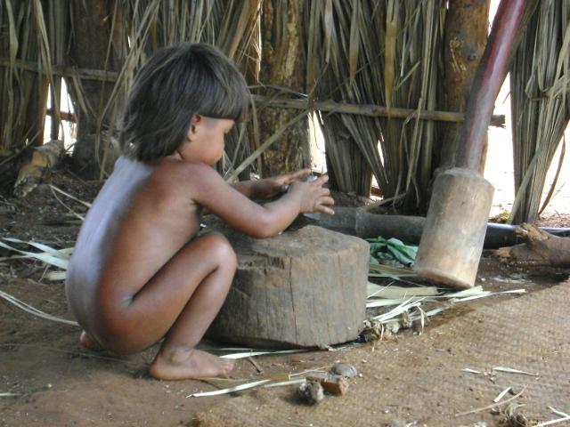 Menino xavante quebrando coquinho do cerrado para comer. Aldeia Etenhiritipá, MT. Foto: Camila Gauditano.