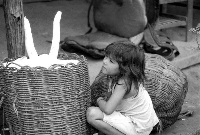 Criança e cassuás com mandioca, em Sapucaeira. Foto: Susana Viegas, 1998