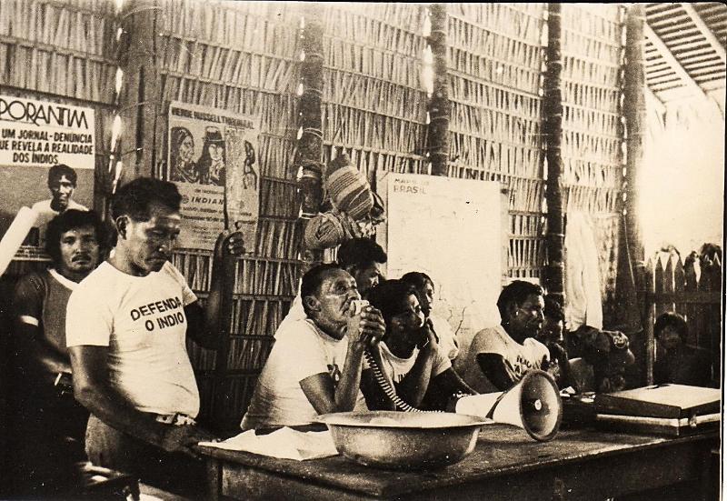 Em pé, Tuxaua Geral do rio Andirá Donato Lopes da Paz segurando o Porantim, com o megafone Tuxaua Geral do rio Marau Emílio Tibúrcio, Assembleia Geral do Povo Sateré-Mawé em 1981 após a invasão da Elf-Aquitaine. Fonte desconhecida.